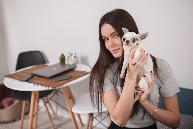 Belle jeune femme souriante à la caméra, restant à la maison avec son chien mignon
