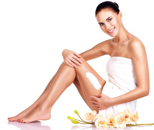 Belle jeune femme souriante avec des fleurs à l'aide de la crème. isolé sur blanc