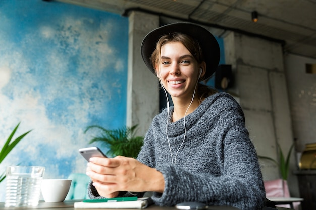 Belle jeune femme souriante habillée en pull et chapeau assis dans une chaise à la table du café, écouter de la musique avec des écouteurs, à l'aide de téléphone mobile, intérieur élégant