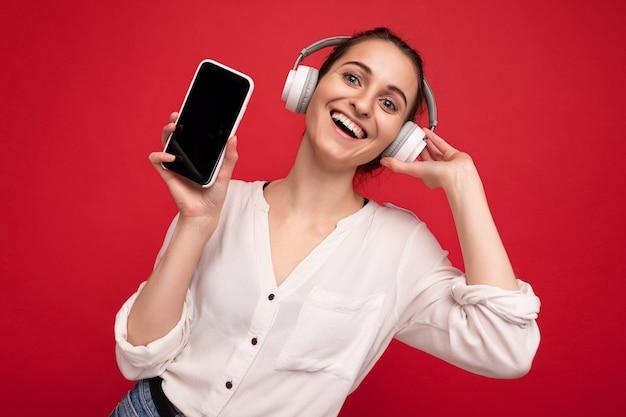 Belle jeune femme souriante et heureuse portant une tenue décontractée élégante isolée sur le mur de fond