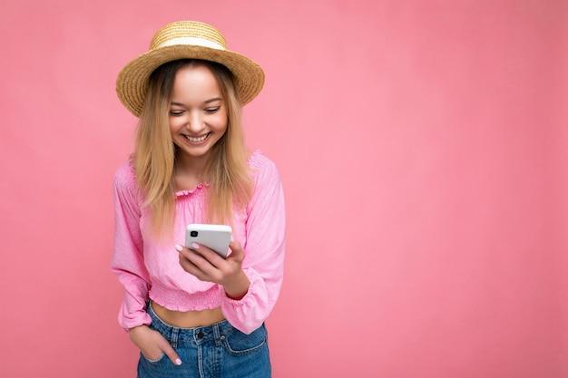 Belle jeune femme souriante et heureuse portant des vêtements décontractés, isolée sur fond, surfant sur internet par téléphone en regardant l'écran du mobile.
