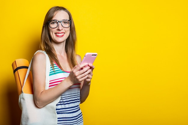 Belle jeune femme souriante avec karimat dans un sac tenant un téléphone sur fond jaune.
