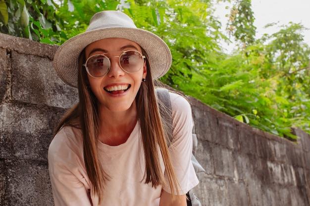 Belle jeune femme souriante à lunettes près des plantes