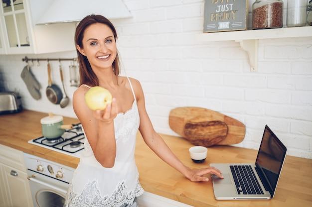 Belle jeune femme souriante mange une pomme dans la cuisine et utilise l'ordinateur portable