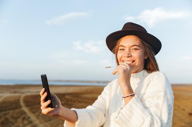 Belle jeune femme souriante marchant à l'extérieur sur la plage pendant le coucher du soleil, prenant un selfie