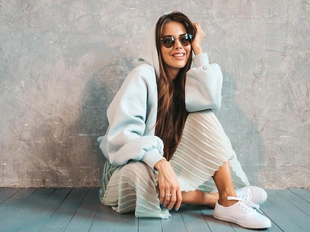 Belle jeune femme souriante montre le signe de la paix. fille à la mode dans des vêtements décontractés à capuche et jupe d'été. assis par terre