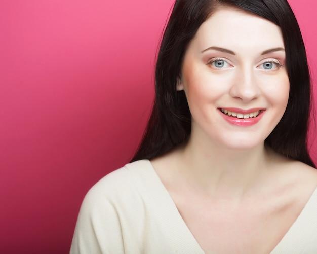 Belle jeune femme souriante avec une peau propre - sur fond rose