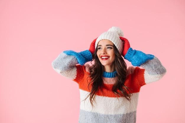 Belle jeune femme souriante portant un pull et un chapeau debout isolé sur rose