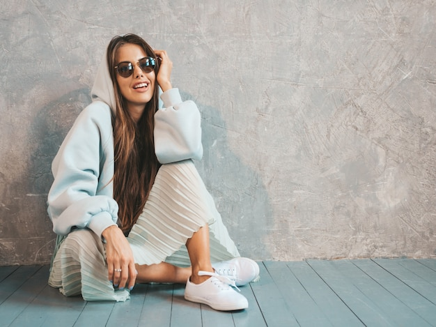 Belle jeune femme souriante à la recherche. fille à la mode dans des vêtements décontractés à capuche et jupe d'été. assis par terre