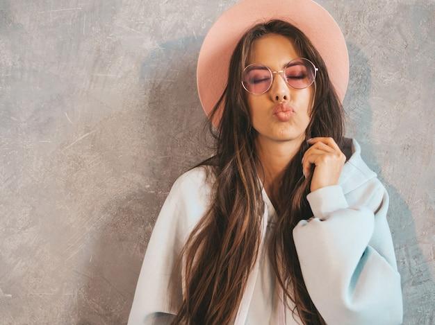 Belle jeune femme souriante à la recherche. fille à la mode dans des vêtements décontractés à capuche et jupe d'été. donner un baiser