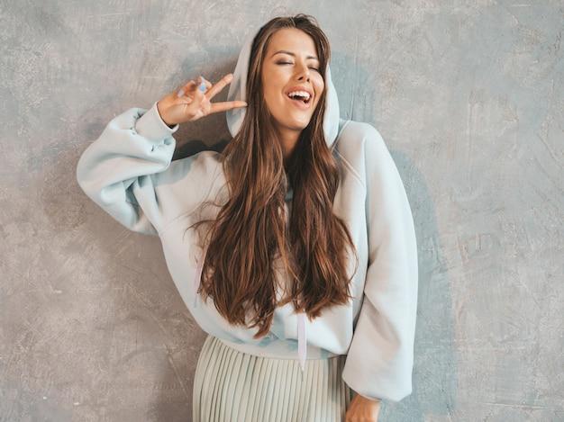 Belle jeune femme souriante à la recherche. fille à la mode dans des vêtements décontractés à capuche et jupe d'été. . montrant le signe de la paix