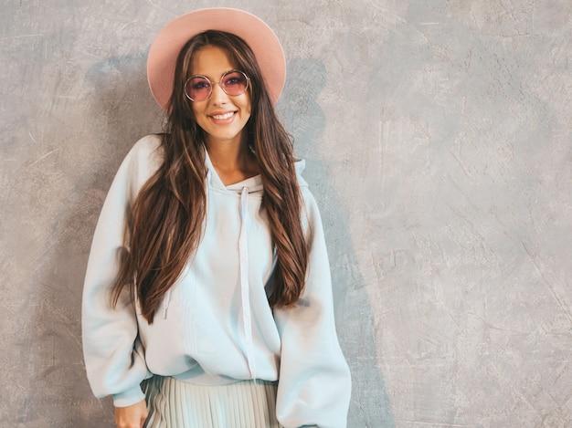 Belle jeune femme souriante à la recherche. fille à la mode dans des vêtements décontractés à capuche et jupe d'été.