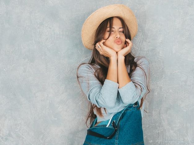 Belle jeune femme souriante à la recherche. fille à la mode dans des vêtements décontractés de salopette d'été et un chapeau ... faire face au canard