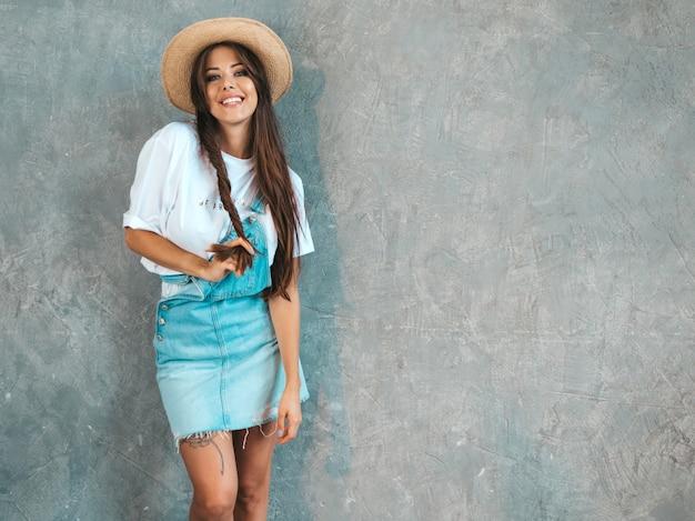 Belle jeune femme souriante à la recherche. fille à la mode dans des vêtements de salopette d'été décontractée et un chapeau.
