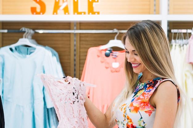 Belle jeune femme souriante regardant robe dans la boutique