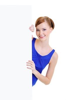 La belle jeune femme souriante regarde à cause d'une bannière publicitaire blanche vide