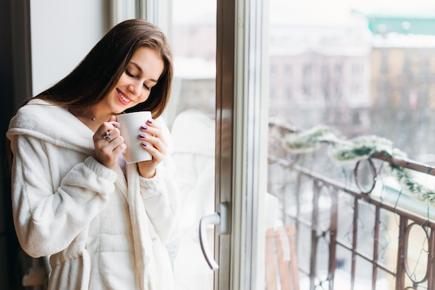Belle jeune femme souriante rêvant debout près de la fenêtre et tenant une tasse de thé ou de café. au milieu du doux soleil du matin brille à travers la vitre. matin calme et ensoleillé.