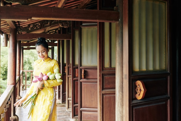 Belle jeune femme souriante en robe ao dai debout sur le porche avec bouquet de fleurs de lotus