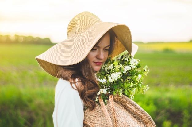 Belle jeune femme souriante en robe vintage et chapeau de paille dans les fleurs sauvages du champ. la jeune fille tient un panier avec des fleurs