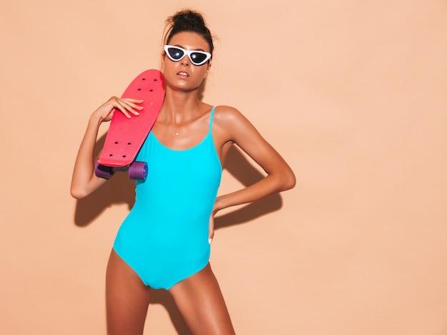Belle jeune femme souriante sexy hipster en lunettes de soleil. fille à la mode en maillot de bain d'été maillot de bain. femme positive devenir fou avec planche à roulettes penny rose, isolé sur mur beige