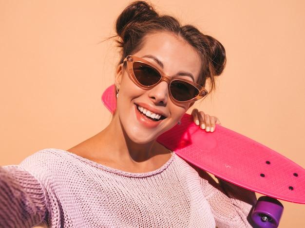 Belle jeune femme souriante sexy hipster en lunettes de soleil.tendance fille en été cardigan tricoté.femme avec planche à roulettes penny rose, isolé sur mur beige.prendre des photos d'autoportrait selfie sur phon