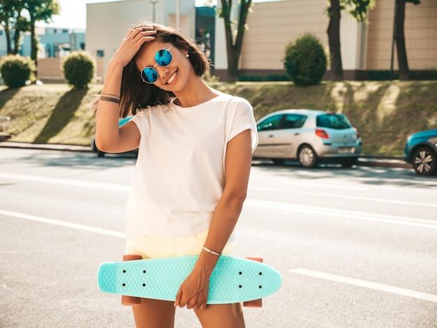 Belle jeune femme souriante sexy hipster en lunettes de soleil.tendance fille en été t-shirt et shorts.femme positive avec skateboard penny bleu posant sur le fond de la rue