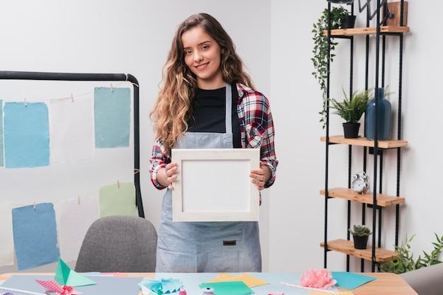 Belle jeune femme souriante tenant le cadre photo vide