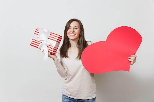 Belle jeune femme souriante tenant un grand coeur rouge, boîte avec cadeau sur fond blanc. copiez l'espace pour la publicité. avec place pour le texte. concept de la saint-valentin ou de la journée internationale de la femme.
