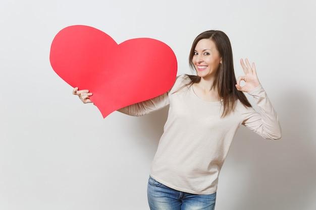 Belle jeune femme souriante tenant un grand coeur rouge, montrant le geste ok sur fond blanc. copiez l'espace pour la publicité. avec place pour le texte. concept de la saint-valentin ou de la journée internationale de la femme