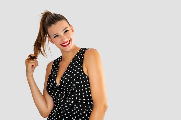 Belle jeune femme souriante et tenant ses cheveux d'une manière coquette, avec une robe noire à pois blancs