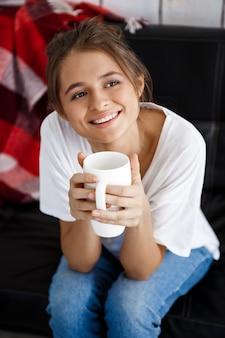 Belle jeune femme souriante, tenant la tasse, assis sur le canapé.