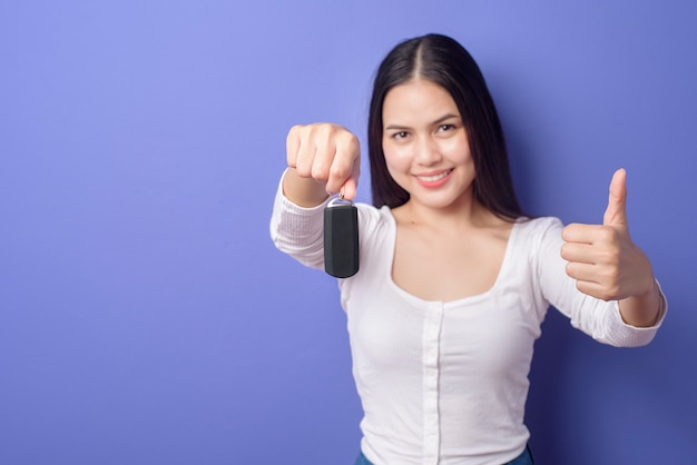 Belle jeune femme souriante tient la clé de voiture sur violet isolé