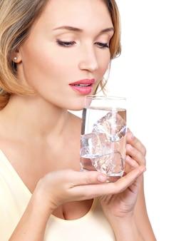 Belle jeune femme souriante avec un verre d'eau sur blanc
