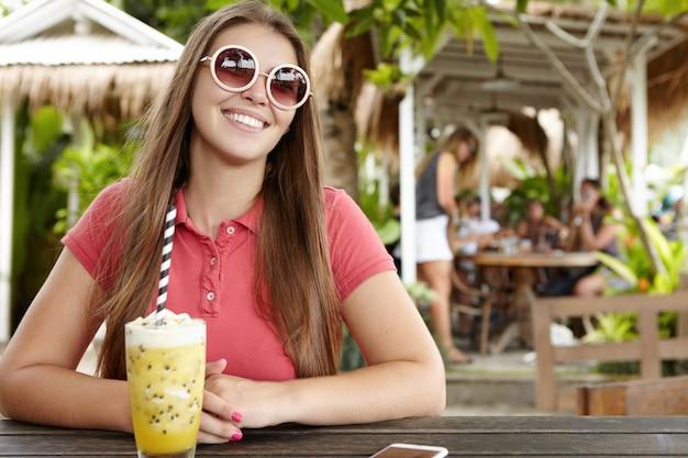 Belle jeune femme avec un sourire charmant ayant une expression heureuse et gaie, profitant de vacances dans un pays exotique