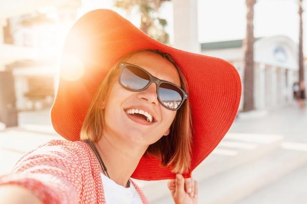 Belle jeune femme sourit joyeusement au soleil dans un grand chapeau rouge vif, concept de vacances et voyage