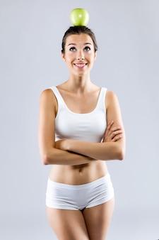 Belle jeune femme en sous-vêtements blancs tenant une pomme verte.