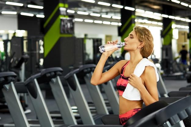 Belle jeune femme sportive au repos après une séance d'entraînement intense dans la salle de gym.