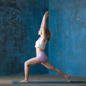 Belle jeune femme sportive faisant pose de lunge haute