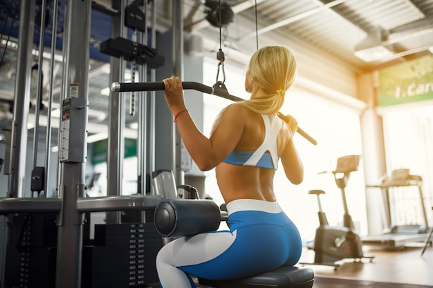 Belle jeune femme sportive posant dans la salle de fitness