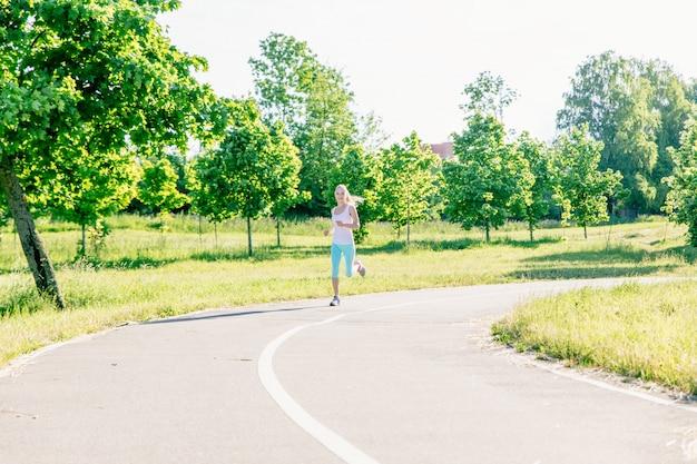 Belle jeune femme sportive qui court dans le parc