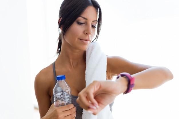 Belle jeune femme sportive à la recherche de son smartwatch à la maison.