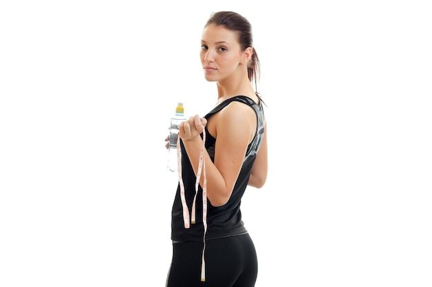 Belle jeune femme sportive se tient le dos à la caméra et garde le ruban à mesurer et l'eau isolé sur un mur blanc