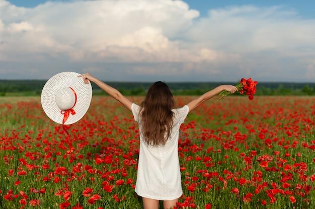 Belle jeune femme style vivant tient dans les mains chapeau blanc et se tient à bras ouverts sur le champ de coquelicots rouges
