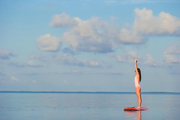 Belle jeune femme surfer sur stand up paddle en vacances exotiques
