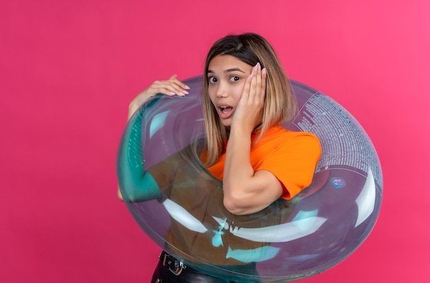 Une belle jeune femme surprise dans un t-shirt orange en gardant la main sur le visage en se tenant debout sur un anneau gonflable sur un mur rose