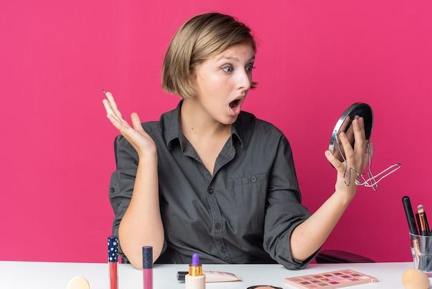 Une belle jeune femme surprise est assise à table avec des outils de maquillage tenant un pinceau de maquillage regardant un miroir dans sa main écartant la main