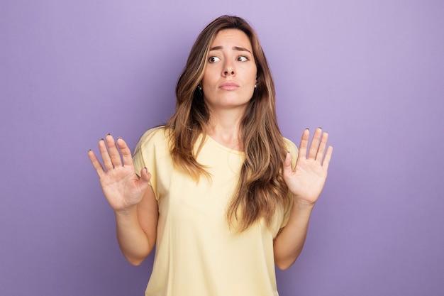 Belle jeune femme en t-shirt beige à côté confus tenant les mains comme dire ne vous approchez pas