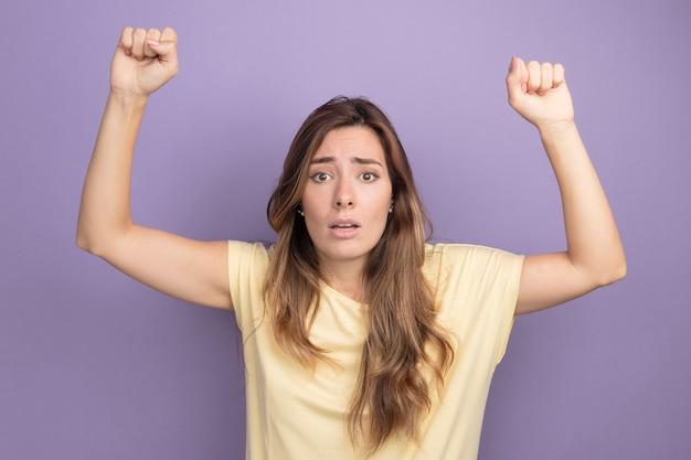 Belle jeune femme en t-shirt beige semblant inquiète avec le poing levé debout sur violet