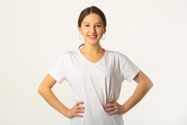 Belle jeune femme en t-shirt blanc sur fond blanc