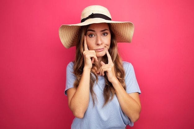 Belle jeune femme en t-shirt bleu et chapeau d'été regardant la caméra avec une expression sceptique